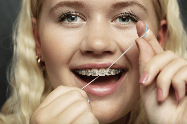 Girl with braces flossing